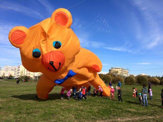 Воздушный змей оранжевого цвета в форме медведя летает над детьми на поле на фоне города