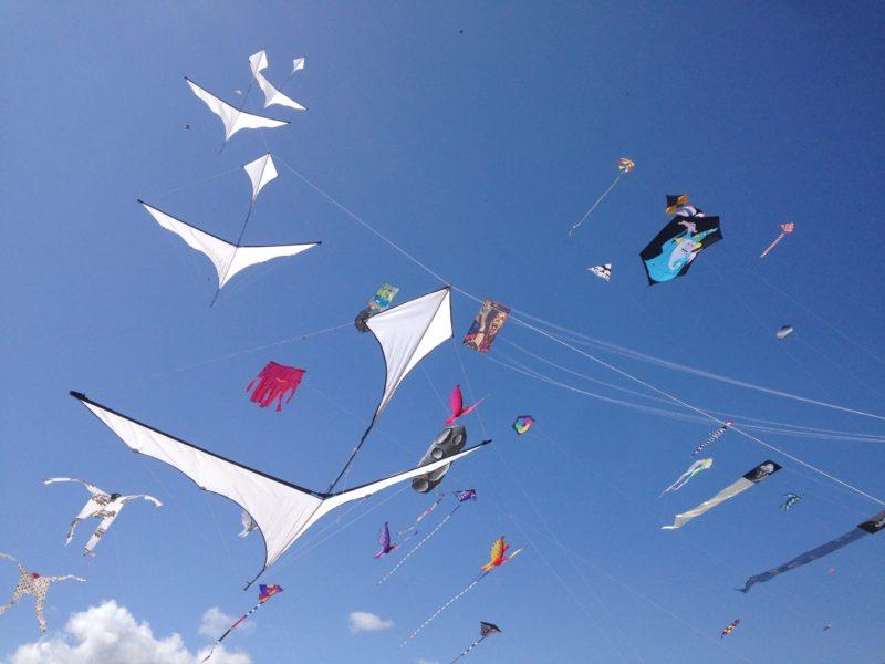 ВОздушные змеи в форме людей, астероидов, птиц, треугольной формы с хвостами, с риснуком волешбника на фоне голубого неба