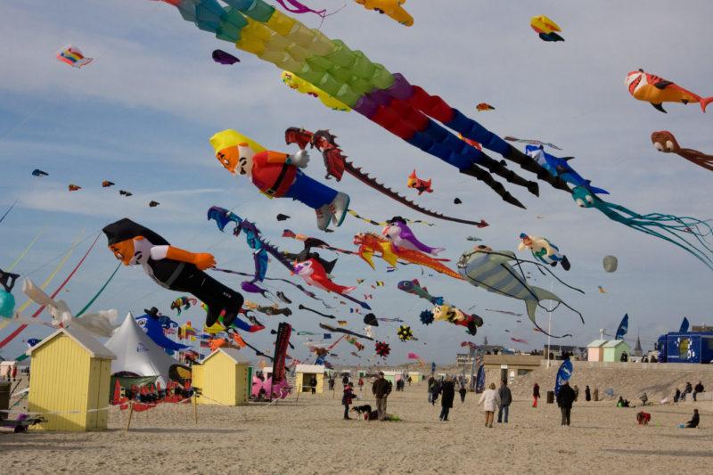 Над морским пляжем летают воздушные змеи в форме гномов, рыб, драконов, осьминогов, акул