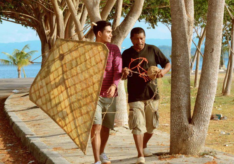 Два человека на тропическом острове идут по берегу моря и несут воздушный змей ромбовидной формы, сделаный из листьев