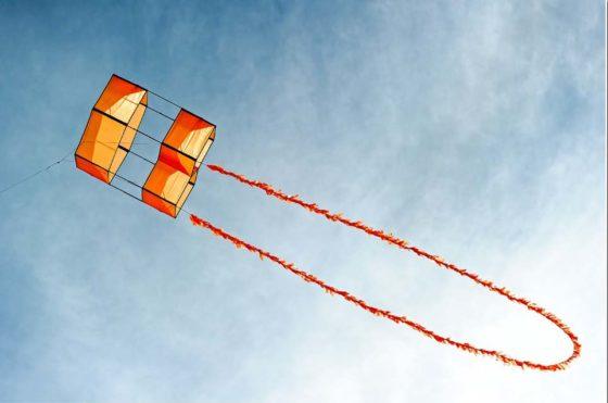 Оранжевый коробчатый змей с хвостом-мишурой на фоне голубого неба