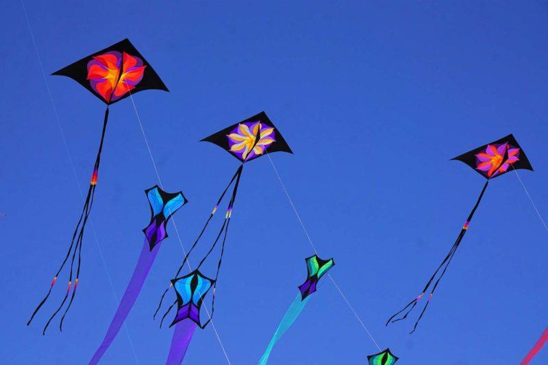 Воздушные змеи с геометрическими рисунками и хвостами на фоне голубого неба
