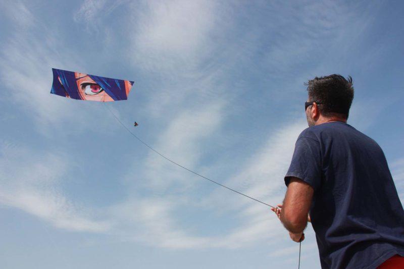 Человек запускает воздушный змей с рисунком в стиле анимэ